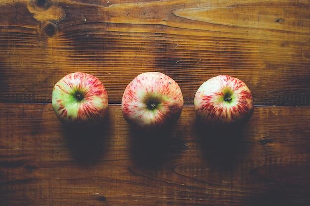 Drei frische reife äpfel auf einem hölzernen Premium Fotos