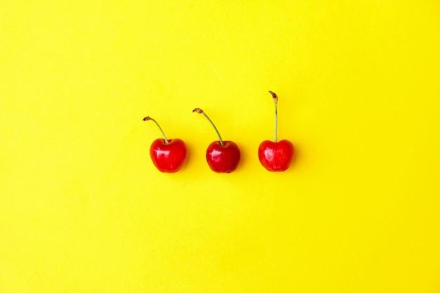 Drei frische rote kirschen auf gelbem hintergrund, werbung, plakat. Premium Fotos