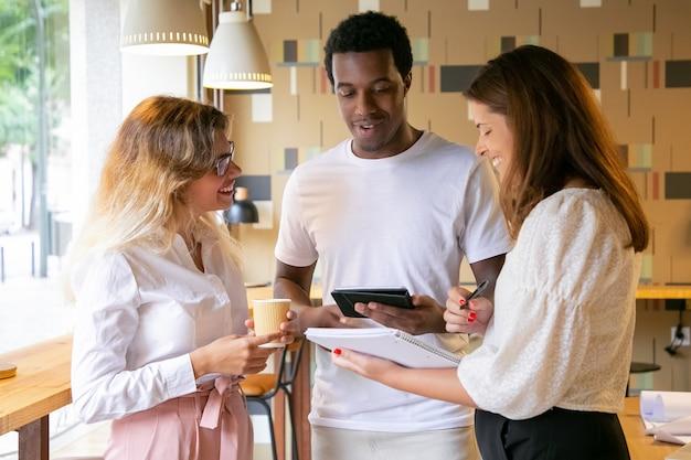 Drei fröhliche designer, die zusammen stehen, lächeln und sprechen Kostenlose Fotos
