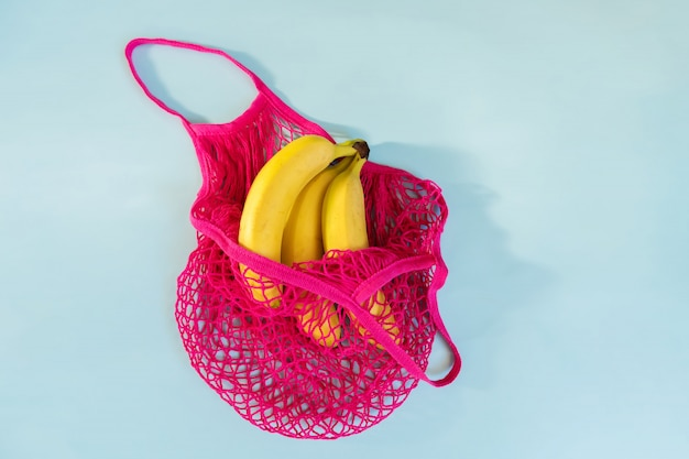 Drei gelbe reife bananen in einer pinkfarbenen eco-baumwollschnurtasche Premium Fotos