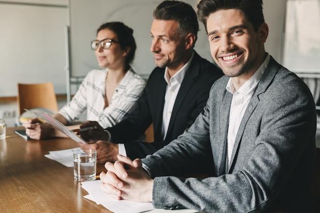 Drei geschäftsführer oder geschäftsführer in formellen anzügen sitzen im büro am tisch und befragen neue mitarbeiter für das teamwork-, karriere- und vermittlungskonzept Premium Fotos