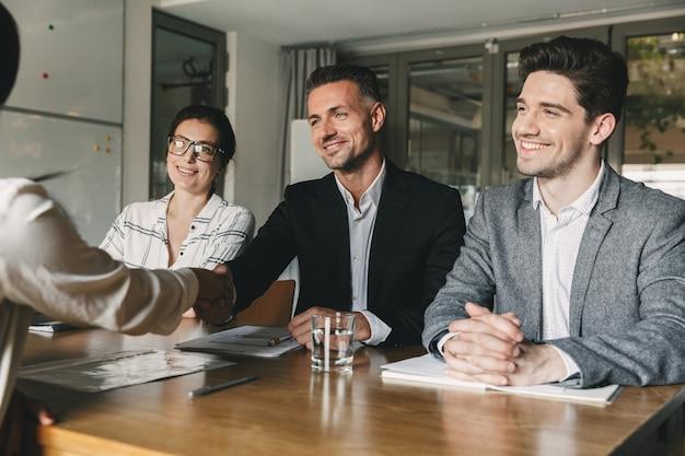 Drei geschäftspartner im büro händeschütteln mit frau, als ergebnis einer erfolgreichen zusammenarbeit oder beginn einer partnerschaft nach effektiven verhandlungen Premium Fotos