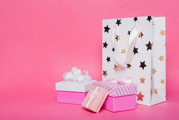 Drei geschenkboxen und einkaufspapiertüte auf rosa hintergrund Kostenlose Fotos