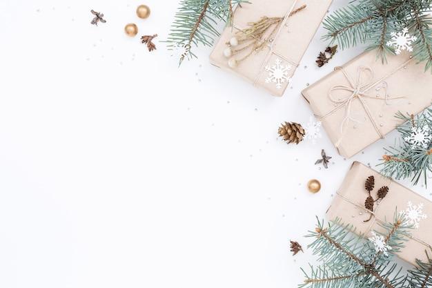 Drei geschenkboxen, weihnachtsschmuck, fichtenzweige auf weißem hintergrund. speicherplatz kopieren. Premium Fotos