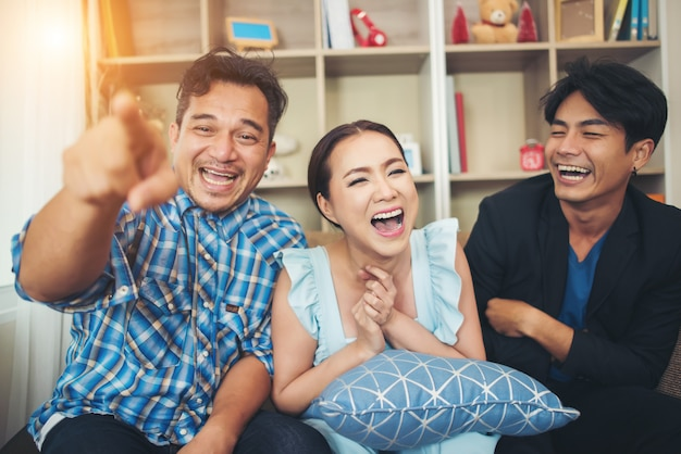 Drei glückliche freunde, die sprechen und großes lachen, nachdem sie witzgeschichte beobachtet haben Kostenlose Fotos