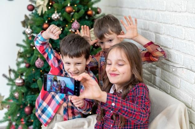 Drei glückliche kinder machen selfie in der nähe des weihnachtsbaumes. glückliche familie Premium Fotos
