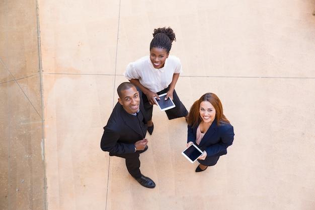 Drei glückliche menschen mit tablet posieren Kostenlose Fotos