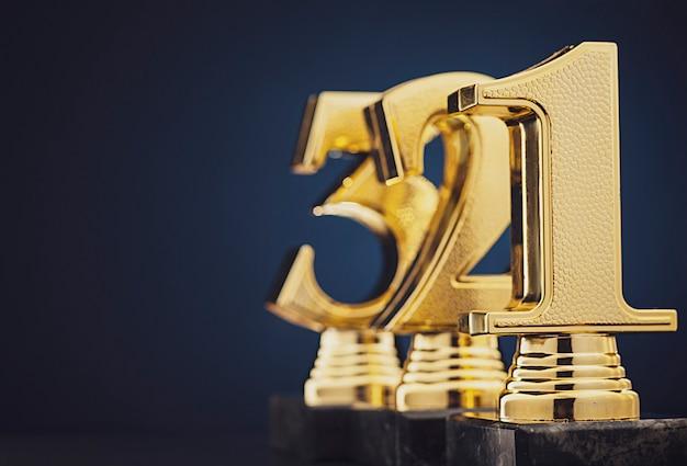 Drei goldene trophäen vor blau Premium Fotos