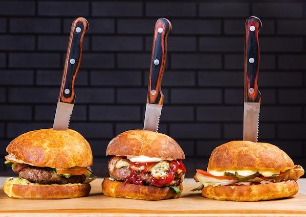 Drei große burger auf holztisch auf schwarzem ziegelsteinhintergrund im restaurant. fast food Premium Fotos