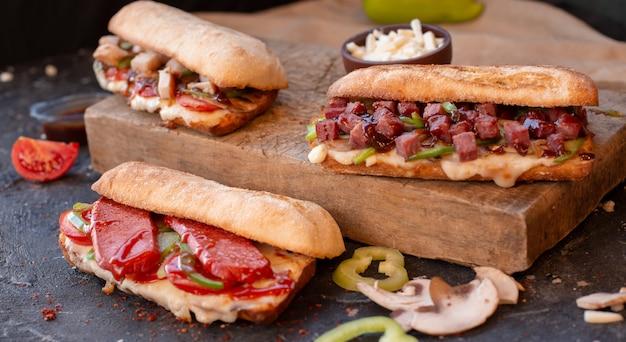 Drei große portionsstangenbrotsandwiche mit mischnahrungsmitteln. Kostenlose Fotos
