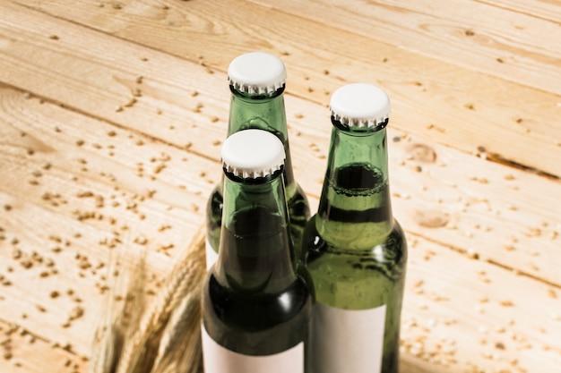 Drei grüne alkoholische flaschen und ohren weizen auf hölzerner planke Kostenlose Fotos