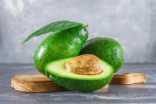 Drei grüne rohe reife avocadofrüchte und ein schnitt halb mit einem knochen mit blättern Premium Fotos