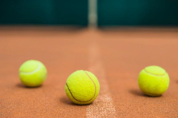 Drei grüne tennisbälle auf dem tennisplatz Kostenlose Fotos
