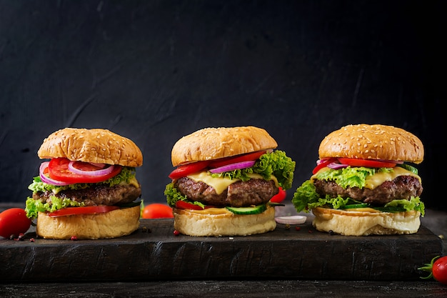 Drei hamburger mit rindfleischfleischburger und frischgemüse auf dunklem hintergrund. Premium Fotos