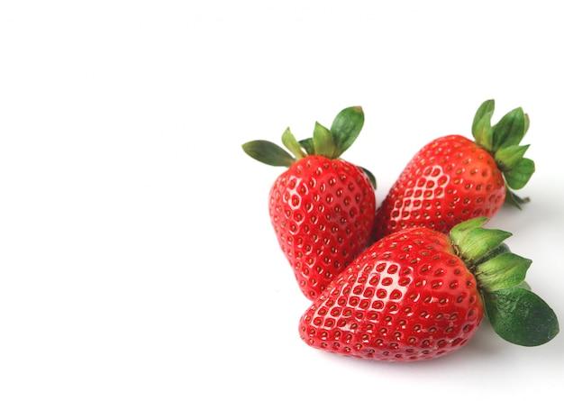 Drei helle farbrote frische reife erdbeeren lokalisiert auf weißem hintergrund mit freiem spac Premium Fotos