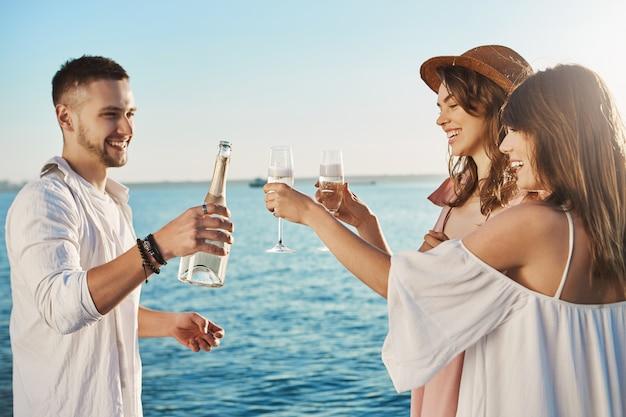 Drei junge attraktive und trendige leute, die über dem meer stehen und trinken, während sie breit lächeln und über etwas sprechen. kollegen verbringen ihre freizeit auf einer party, die ihre firma arrangiert hat. Kostenlose Fotos