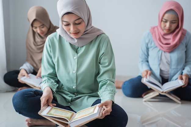 Drei junge frauen, die hijabs tragen, lesen das heilige buch des korans Premium Fotos