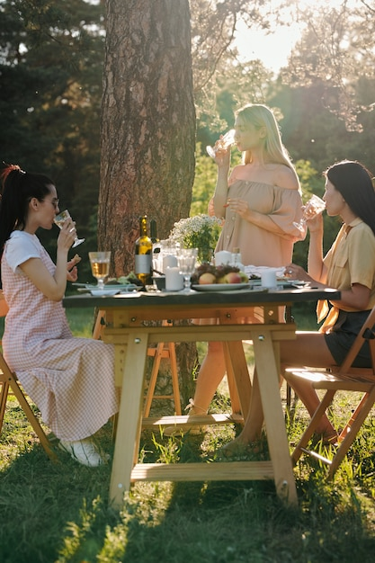 Drei junge frauen in freizeitkleidung, die getränke am servierten tisch nach dem abendessen im freien unter kiefer am sonnigen sommertag haben Premium Fotos