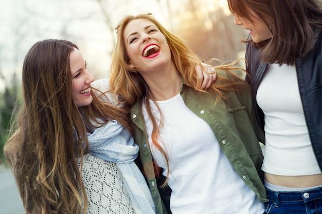 Drei junge frauen reden und lachen auf der straße. Kostenlose Fotos