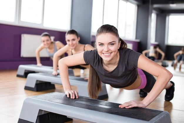 Drei junge frauen trainieren mit steppern im fitnessstudio. Premium Fotos