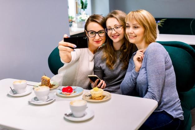 Drei junge freundinnen - drei mädchen, die an einem tisch in einem café sitzen, plaudern, lächeln, kaffee aus weißen tassen trinken, desserts essen und selfies machen. lifestyle, casual, kommunikationsfreude. Premium Fotos
