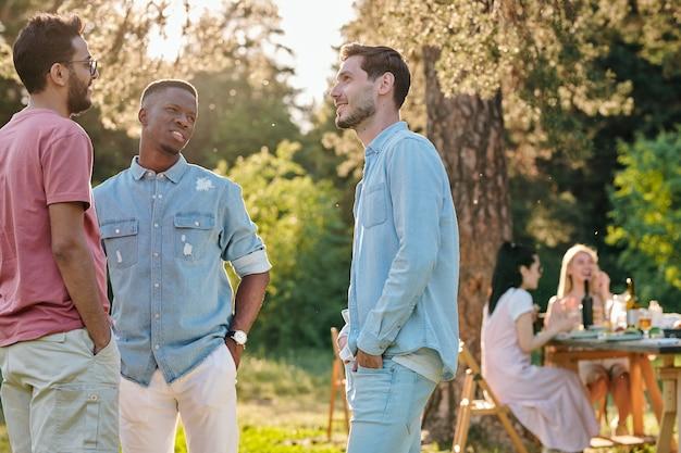 Drei junge interkulturelle männer in freizeitkleidung, die am sommertag auf grünem rasen stehen und reden Premium Fotos