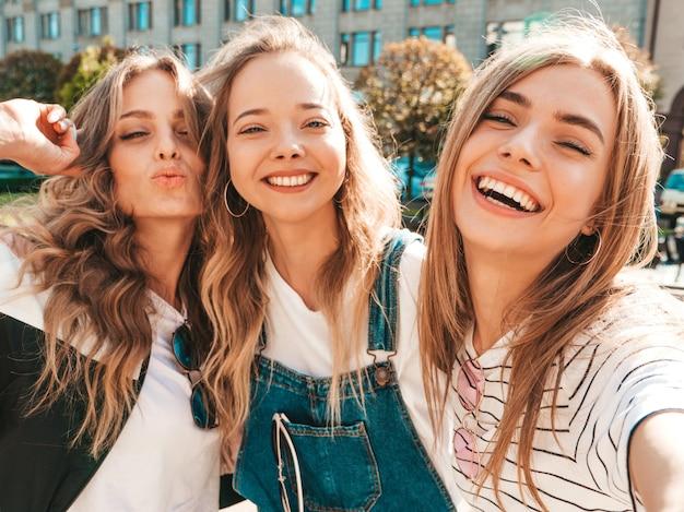 Drei junge lächelnde hippie-frauen in der sommerkleidung mädchen, die selfie selbstporträtfotos auf smartphone machen modelle, die in der straße aufwerfen frauen, die positive gesichtsgefühle zeigen Kostenlose Fotos