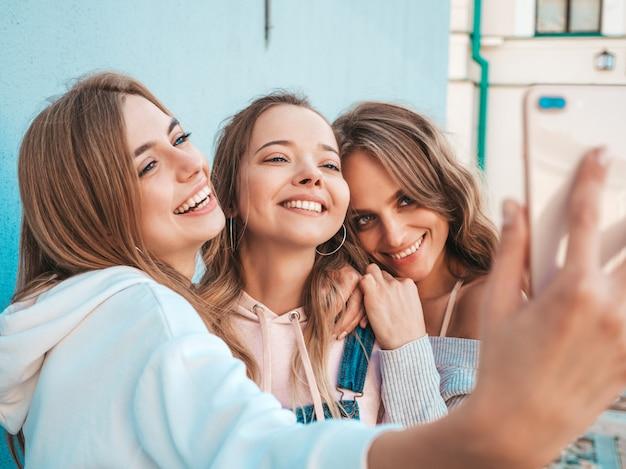 Drei junge lächelnde hippie-frauen in der sommerkleidung mädchen, die selfie selbstporträtfotos auf smartphone machen modelle, die in der straße nahe wand aufwerfen frauen, die positive gesichtsgefühle zeigen Kostenlose Fotos