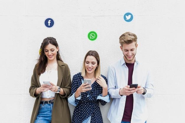 Drei junge leute, die verschiedene social media-websites an ihrem handy verwenden Kostenlose Fotos