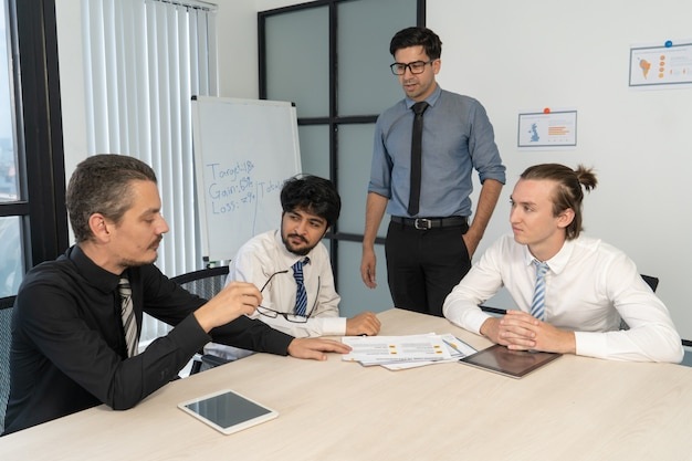 Drei junge manager, die zu ernstem chef berichten. Kostenlose Fotos