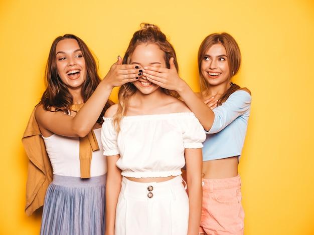 Drei junge schöne lächelnde hippie-mädchen in der modischen sommerkleidung sexy sorglose frauen, die nahe gelber wand aufwerfen modelle, die ihren freund überraschen sie bedecken ihre augen und von hinten umarmen Kostenlose Fotos