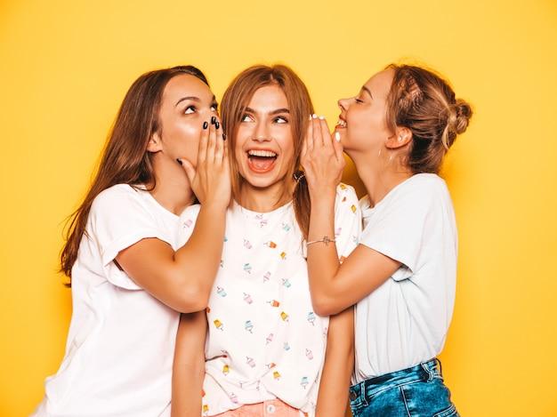 Drei junge schöne lächelnde hippie-mädchen in der modischen sommerkleidung. sexy sorglose frauen, die nahe gelber wand aufwerfen. positive models werden verrückt und haben spaß. teilen sie geheimnisse, klatsch und tratsch Kostenlose Fotos