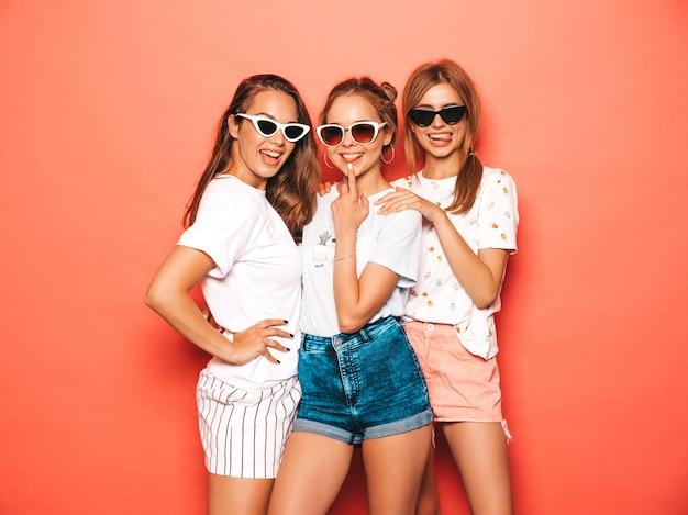 Drei junge schöne lächelnde hippie-mädchen in der modischen sommerkleidung. sexy sorglose frauen, die nahe rosa wand aufwerfen. positive models werden verrückt und haben spaß mit sonnenbrillen Kostenlose Fotos