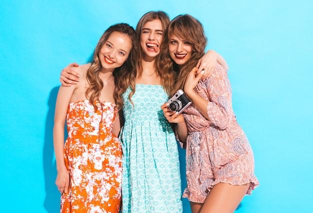 Drei junge schöne lächelnde mädchen in den beiläufigen kleidern des modischen sommers. sexy sorglose frauenaufstellung. fotografieren mit der retro-kamera. zeigt die zunge Kostenlose Fotos