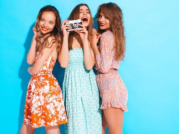 Drei junge schöne lächelnde mädchen in den beiläufigen kleidern des modischen sommers. sexy sorglose frauenaufstellung. fotografieren mit der retro-kamera Kostenlose Fotos