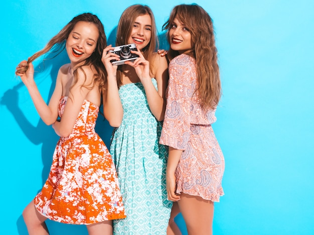 Drei junge schöne lächelnde mädchen in den bunten kleidern des modischen sommers. sexy sorglose frauenaufstellung. fotografieren mit der retro-kamera Kostenlose Fotos