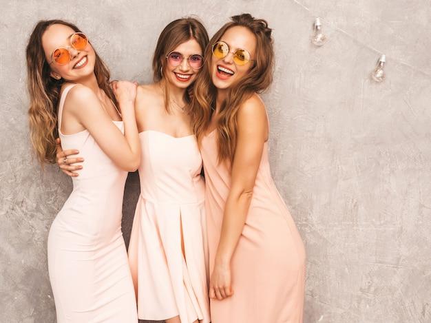 Drei junge schöne lächelnde mädchen in den hellrosa kleidern des modischen sommers. sexy sorglose frauenaufstellung. positive models in runder sonnenbrille haben spaß Kostenlose Fotos