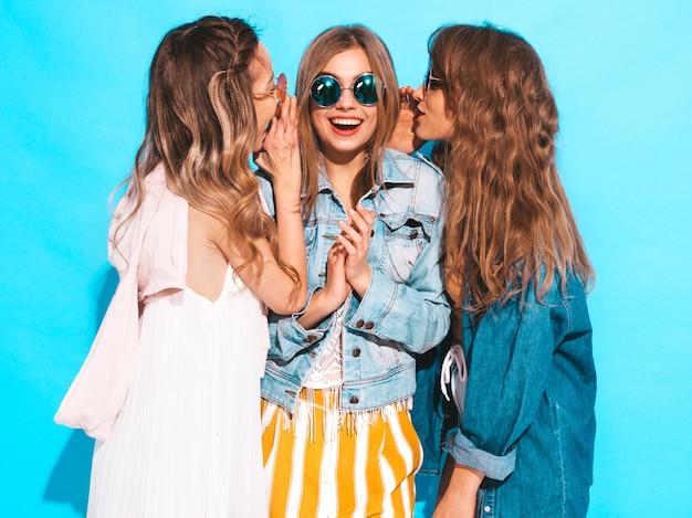 Drei junge schöne lächelnde mädchen in der beiläufigen kleidung des modischen sommers. sexy frauen teilen geheimnisse, klatsch. lokalisiert auf blau. Kostenlose Fotos