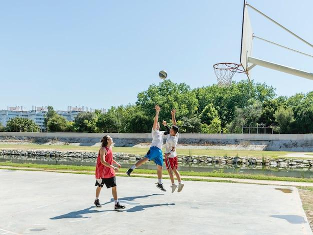 Drei junge spieler auf dem basketballplatz Kostenlose Fotos