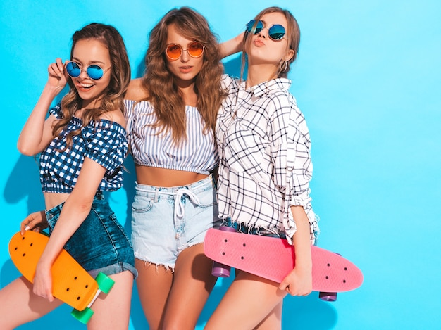 Drei junge stilvolle lächelnde schöne mädchen mit bunten pennyskateboards. frauen in der sommerkleidung, die in der sonnenbrille aufwirft. positive models, die spaß haben Kostenlose Fotos