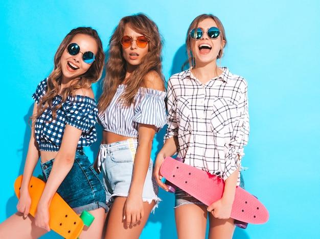 Drei junge stilvolle sexy lächelnde schöne mädchen mit bunten pennyskateboards. frauen im sommer kariertes hemd kleidung in sonnenbrillen. positive models, die spaß haben Kostenlose Fotos