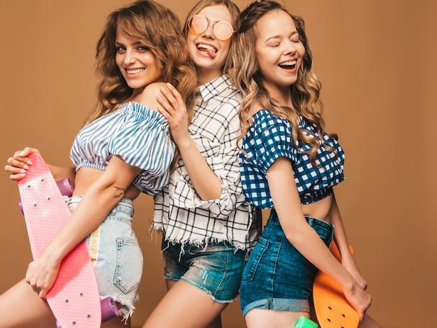 Drei junge stilvolle sexy lächelnde schöne mädchen mit bunten pennyskateboards. frauen in der karierten hemdkleidung des sommers, die in der sonnenbrille aufwirft. positive models, die spaß haben Kostenlose Fotos