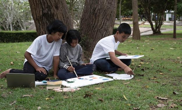 Drei kinder sitzen auf grünem gras im erdgeschoss und malen farbe auf leinwand. sie tun aktivität zusammen mit einem glücklichen gefühl in einem park Premium Fotos
