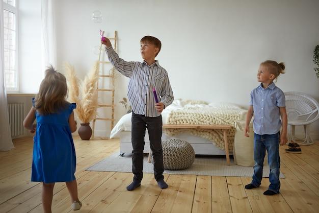 Drei kinder spielen zu hause zusammen. schuljunge in hemd