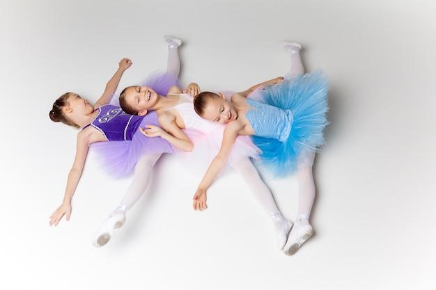 Drei kleine ballettmädchen im ballettröckchen, das zusammen liegt und aufwirft Kostenlose Fotos