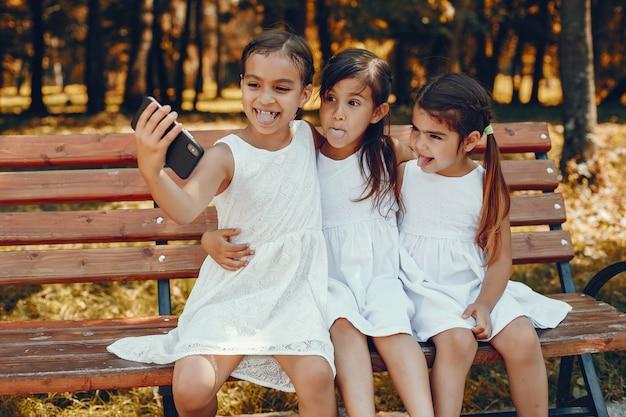 Drei kleine schwestern, die in einem sommerpark sitzen Kostenlose Fotos