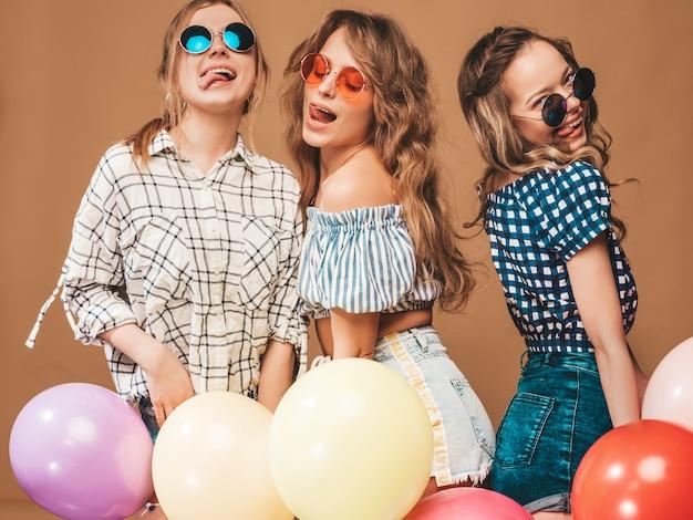 Drei lächelnde schönheiten im karierten hemdsommer kleidet. mädchen posieren. modelle mit bunten luftballons in sonnenbrillen. spaß haben, bereit zum feiergeburtstag Kostenlose Fotos