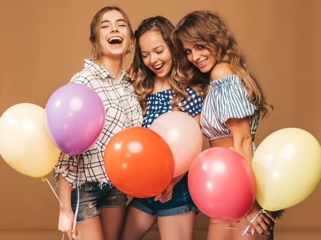 Drei lächelnde schönheiten im karierten hemdsommer kleidet. mädchen posieren. modelle mit bunten luftballons. spaß haben, bereit zum feiergeburtstag Kostenlose Fotos