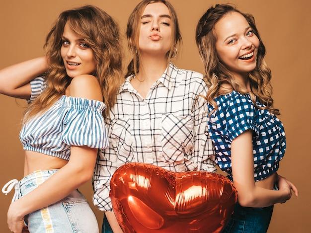 Drei lächelnde schönheiten im karierten hemdsommer kleidet. mädchen posieren. modelle mit herzformballon. bereiten sie für feier valentinstag vor Kostenlose Fotos