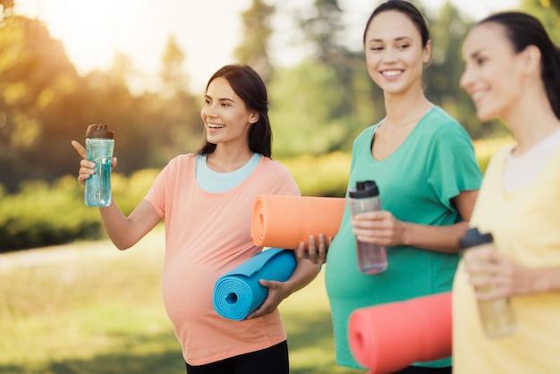 Drei lächelnde schwangere mädchen mit yoga-matten. Premium Fotos